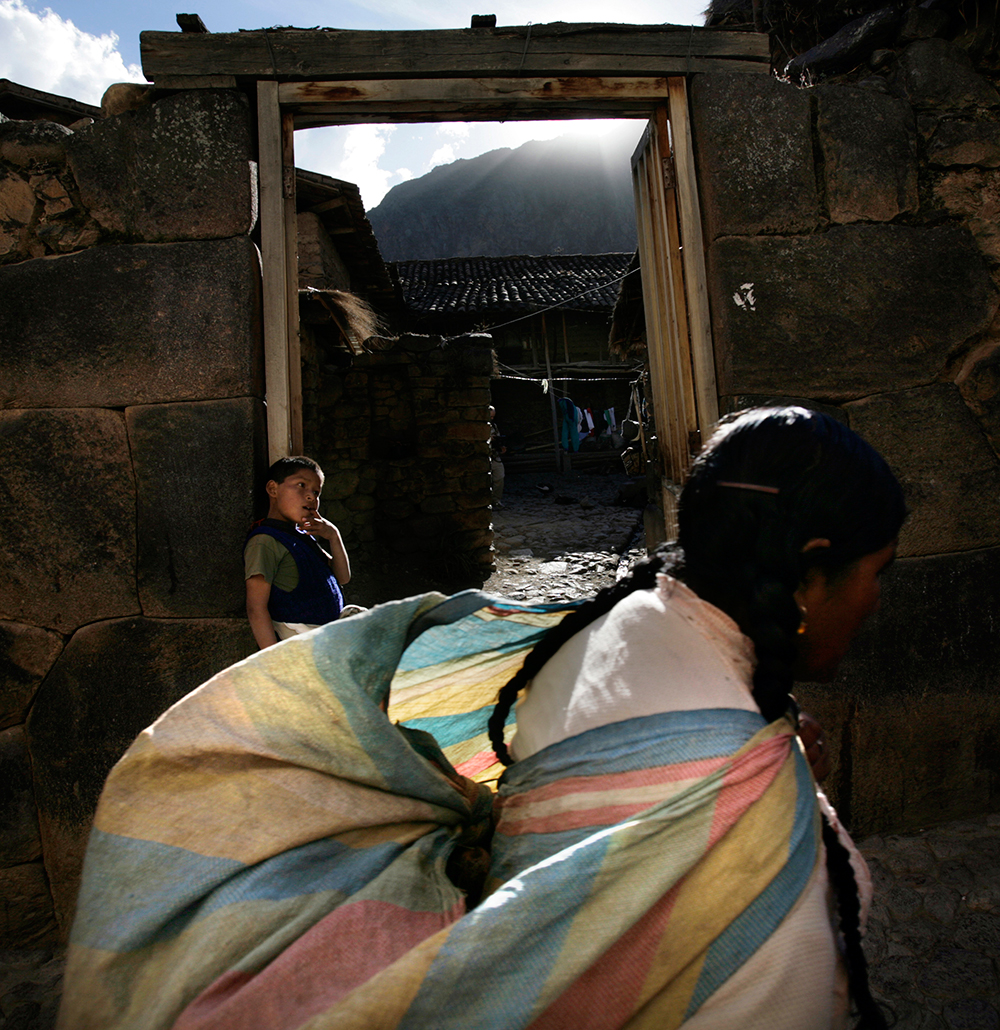 A woman walks through the town of Ollantaytambo. Photo by Karla Gachet/Panos.